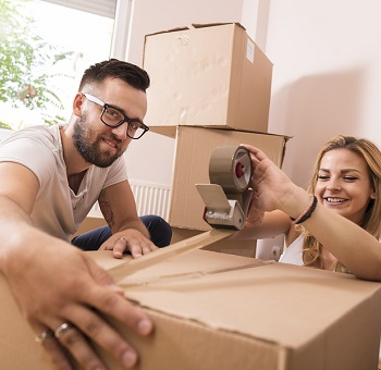 young couple taping boxes for moving with boxes in background