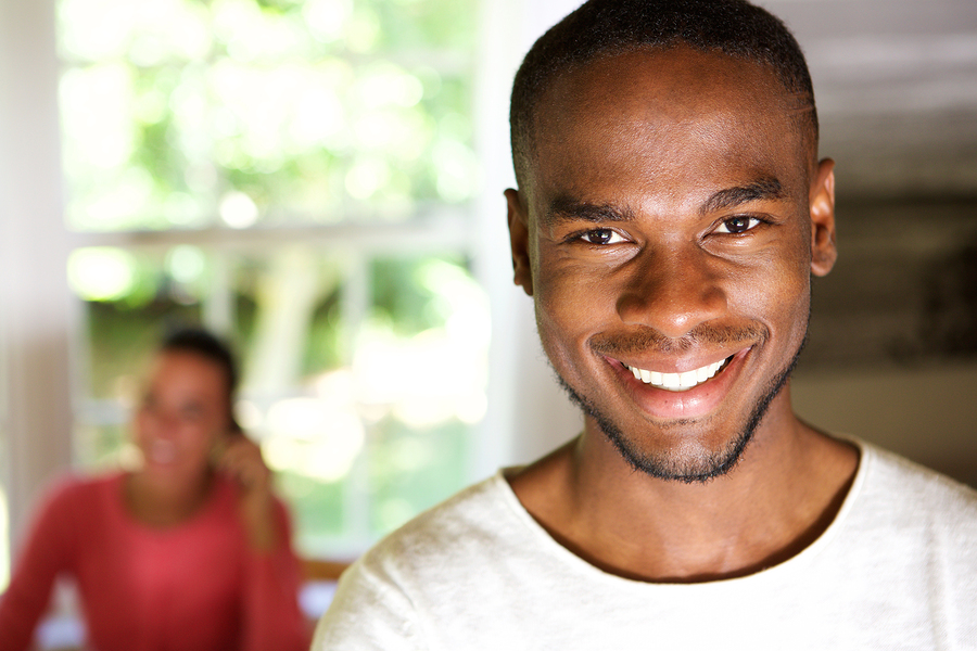 Smiling handsome african man with woman in background